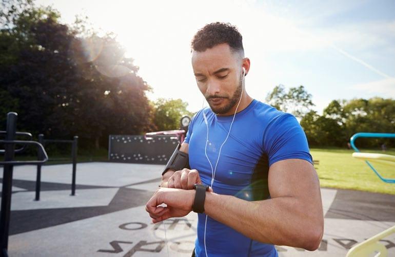 Man draagt sporthorloge tijdens hardlopen.
