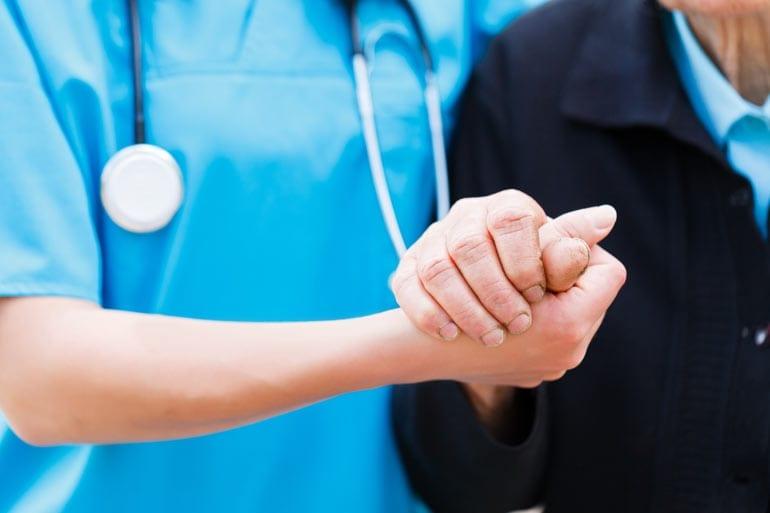 Verpleegster houdt hand van oude man vast.