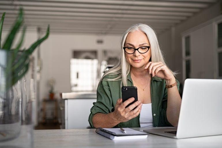 Vrouw werkt thuis met laptop en smartphone.